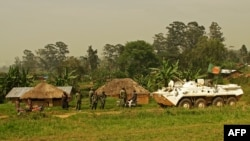 A Bangladeshi patrol from the United Nations Organization Stabilization Mission in the Democratic Republic of the Congo (MONUSCO) passes by Congolese soldiers in Gety, near Kaswara, Ituri province, on Jan. 26, 2016. Renewed fighting in the province has killed dozens of people and created a wave of refugees.