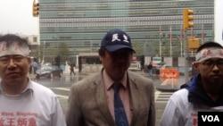 王炳章的弟弟王炳武(左)、中国民主党全国委员会共同主席王军涛和党员杨维锋在纽约联合国大楼前淋雨请愿。(美国之音方方拍摄)