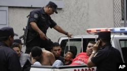 Thành viên của băng đảng MS-13 bị bắt vì các tội sát nhân và sở hữu súng trở lên xe cảnh sát sau khi được đưa ra trình diện trước các nhà báo trong thủ đô San Salvador của El Salvador