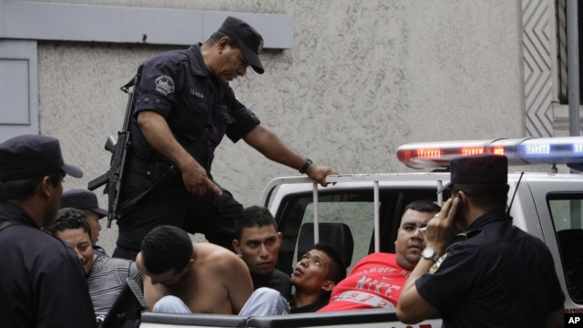 In this Aug. 31, 2012 photo, alleged members of the MS-13 or Mara Salvatrucha gang arrested on murder and gun possession charges are loaded into a police pick-up truck after being presented to the press in San Salvador, El Salvador.