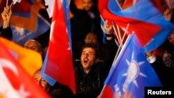 在安卡拉的土耳其执政党正义与发展党总部外面,人们挥舞旗子(2015年11月1日)