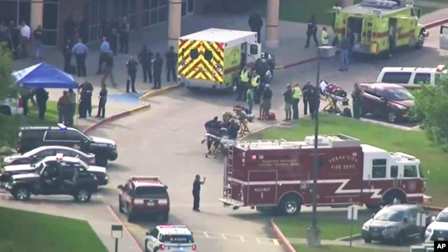 In this image taken from video, emergency personnel and law enforcement officers respond to a high school in Santa Fe, Texas, after an active shooter was reported on campus, May 18, 2018.