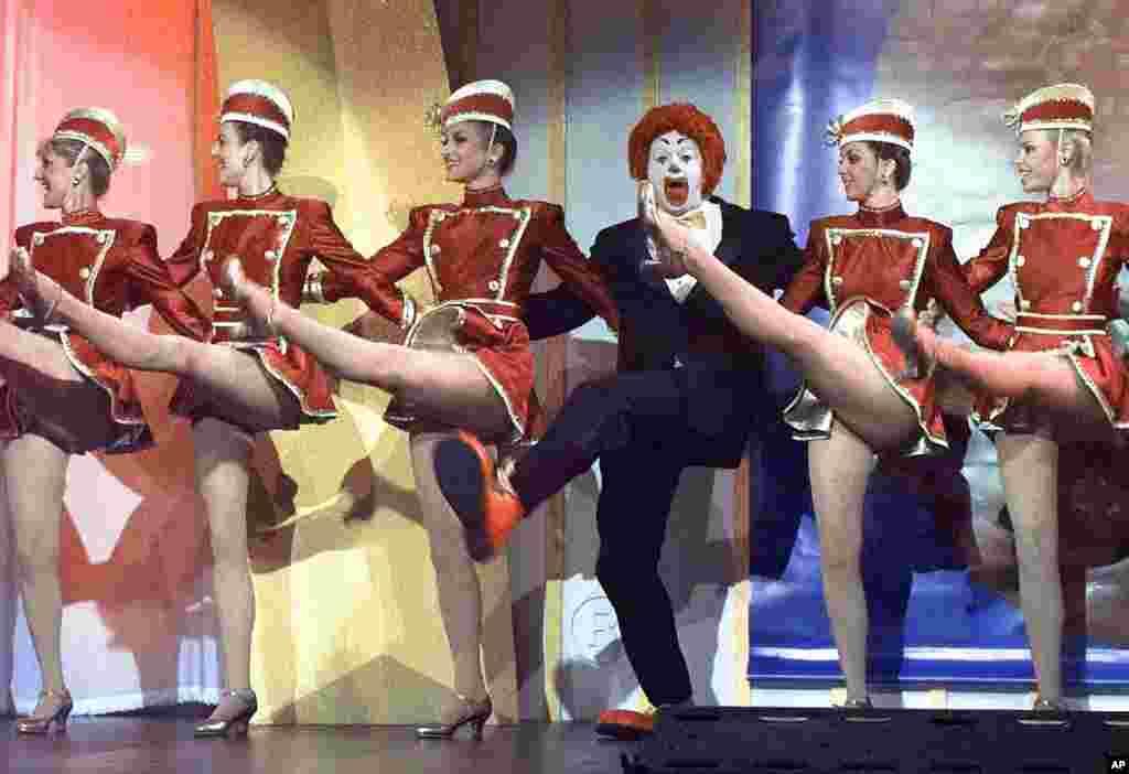 麦当劳餐厅的形象人物罗纳德·麦当劳换上西服,和火箭女郎舞蹈团一起踢腿(1996年)