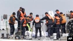 Các cảnh sát thuộc lực lượng Tuần duyên Nam Triều Tiên kiểm tra thi hài các hành khách được đưa từ chiếc phà bị đắm, 20/4/14