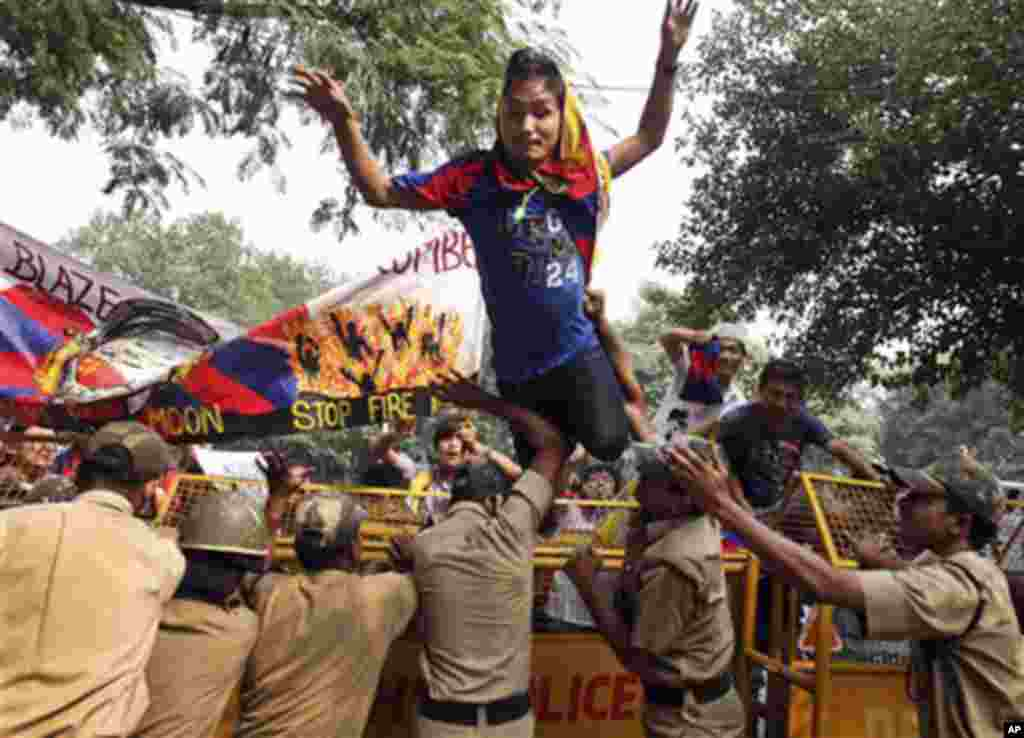 An exile Tibetan jumps over a police barricade outside the United Nations Information Center at a protest seeking U.N. intervention in the Tibet issue in New Delhi, India, Monday, Oct. 24, 2011.