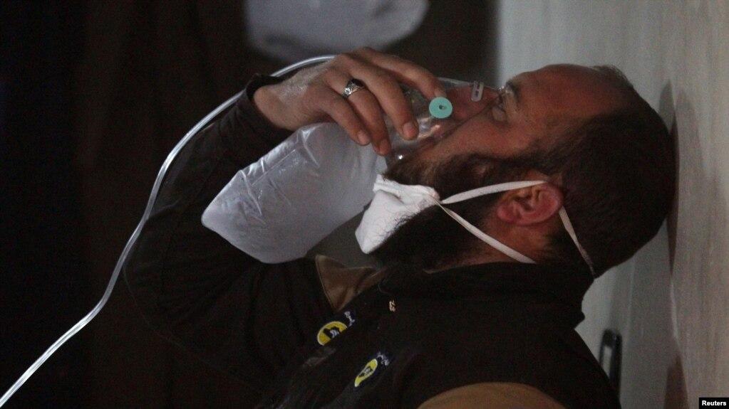 一名民間組織工作人員戴上面罩呼吸。