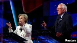 Ứng cử viên tổng thống đảng Dân chủ Hillary Clinton (trái) và Thượng nghị sĩ Bernie Sanders phát biểu đồng thời trong một cuộc tranh luận được tổ chức bởi CNN và New York One tại Brooklyn Navy Yard, New York ngày 14 tháng 4 năm 2016.
