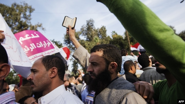 A man holds a copy of the Quran during pro-Morsi rally outside Cairo University, Dec. 1, 2012.