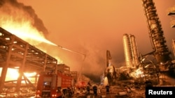 Firefighters try to extinguish a fire at a petrochemical plant in Zhangzhou, Fujian province, April 7, 2015.