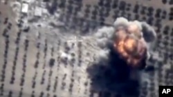 This photo made from the footage taken from Russian Defense Ministry official web site on Oct. 16, 2015 shows a target hit during a Russian air raid in Syria. Russian Defense Ministry said the strike was performed by an Su-24M bomber in Idlib.