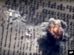 FILE - In this photo made from the footage taken from Russian Defense Ministry official web site on Friday, Oct. 16, 2015 showing a target hit during a Russian air raid in Syria. Russian Defense Ministry said the strike was performed by an Su-24M bomber in Idlib.