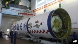 Chinese workers prepare the Long March 2F carrier rocket, to launch the Shenzhou-8 unmanned spacecraft into space. (File Photo - Sept. 25, 2011)