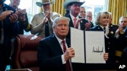 Presiden AS Donald Trump menandatangani veto pertama kepresidenannya, guna mendanai tembok di perbatasan AS-Meksiko, hari Jumat (15/3).