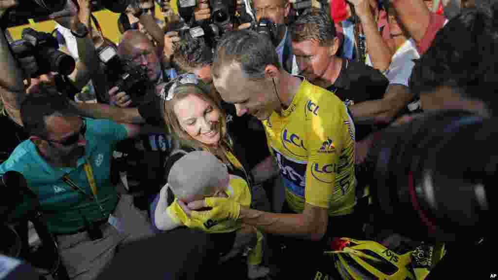 Le champion du Tour de France, Chris Froome, est félicité par son épouse Michelle qui tient son petit garçon, le 14 juillet 2016.