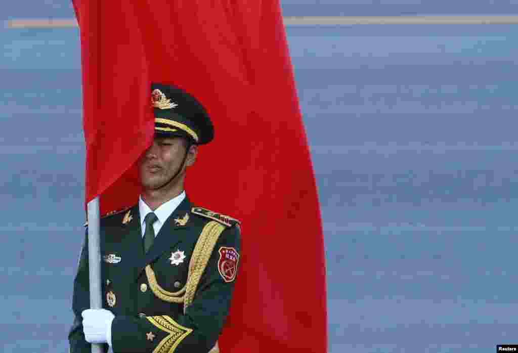 A Chinese honor guard holds a red flag during an official welcoming ceremony for Malaysia's King Abdul Halim at the Great Hall of the People in Beijing.