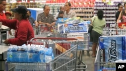 Shoppers stock up on cases of bottled water and other supplies in preparation for a hurricane and tropical storm heading toward Hawaii at the Iwilei Costco in Honolulu, Aug. 5, 2014.