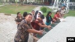 Umat yang melakukan cuci tangan sebelum mengikuti misa di Gereja Katolik Santa Maria Palu (22/3/) (Foto: VOA/Yoanes Litha).