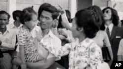 Neou Sarem says goodbye to her husband, Nuon Sari, and her 3-year old daugther, Nuon Sari Sakhura, at Pochentong Airport, 1974.