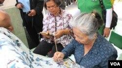 Proses pembuatan batik tulis bertema mangrove oleh perajin dan kader lingkungan Kecamatan Rungkut Surabaya (Foto: VOA/Petrus Riski)