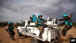 FILE - In this photo released by the United Nations African Union Mission in Darfur (UNAMID), Tanzanian UNAMID troops patrol Khor Abeche, South Darfur, Sudan.