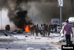 Somalian government forces evacuate their injured colleague, from the scene of an explosion in KM4 street in the Hodan district of Mogadishu, Oct. 14, 2017.