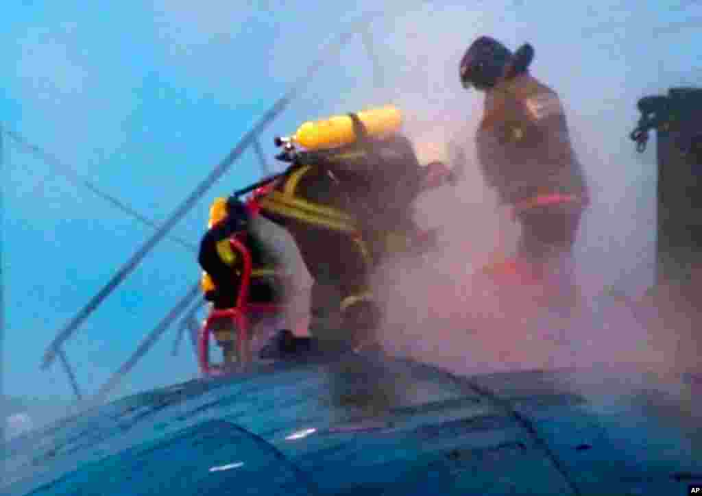 In this video image from Ru-RTR Russian state television channel, firefighters work on the hull of the Yekaterinburg nuclear submarine after a massive fire broke out. (AP Photos)