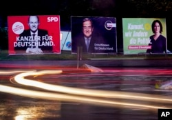 Three elections posters show Social Democratic top candidate for chancellor Olaf Scholz, L, Christian Democratic top candidate Armin Laschet, center, and top candidate of the Greens Annalena Baerbock, R, in Frankfurt, Germany, Sept. 15, 2021.