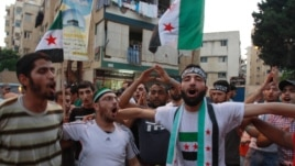 Lebanese and Syrian citizens celebrate reports of the deaths of members of Syrian President Bashar al-Assad's inner cirle at a rally in Tripoli, northern Lebanon, July 18, 2012.