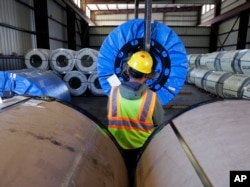 In this Nov. 21, 2016 photo, a worker uses a lift to move rolls of sheet metal at LMS International, in Laredo, Texas. Donald Trump's campaign promise to abandon the North American Free Trade Agreement helped win over Rust Belt voters who felt left behind.