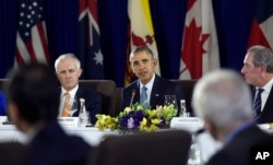 FILE - President Barack Obama, center, sitting next to Australia's Prime Minister Malcolm Turnbull, left, and U.S. Trade Representative Michael Froman, right, speaks during a meeting with other leaders of the Trans-Pacific Partnership countries in Manila, Philippines, Nov. 18, 2015, ahead of an Asia-Pacific Economic Cooperation summit.