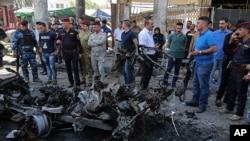 Pasukan keamanan Irak dan warga sipil memeriksa lokasi ledakan bom di Baghdad, Irak, 30 Mei 2017. (AP Photo/Karim Kadim)