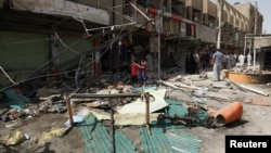 Residents stand amid debris near shops damaged by a car bomb attack that occurred late on Monday in east of Baghdad, Iraq, July 24, 2012.