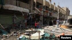 Cư dân đứng giữa những mảnh vụn bên ngoài các cửa hàng bị hư hại sau vụ đánh bom ở phía đông thủ đô Baghdad, ngày 24/7/2012