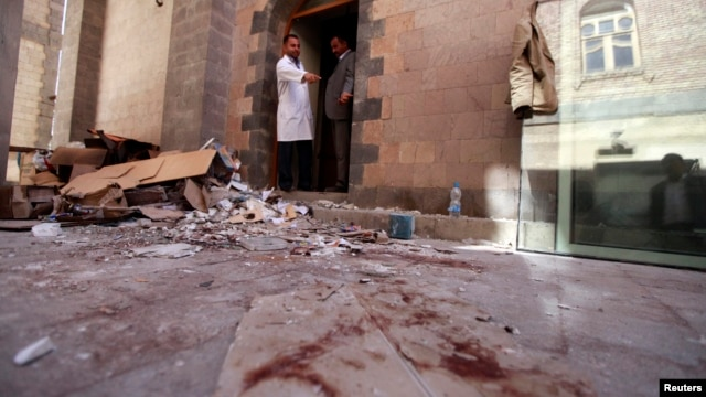 A doctor points at blood inside the hospital at the scene of the attack during a tour for journalists and survivors at the Defense Ministry in Sana'a Dec. 19, 2013.