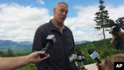 FILE - Interior Secretary Ryan Zinke talks with reporters with part of Mount Katahdin in the background at the Katahdin Woods and Waters National Monument near Staceyville, Maine, June 14, 2017.