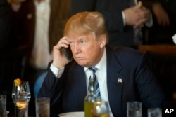 FILE - Then-Republican presidential candidate Donald Trump listens to his mobile phone during a lunch stop in North Charleston, S.C., Feb. 18, 2016. Trump's approach to Twitter has been as unorthodox as his presidential campaign.