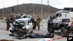 이스라엘 군인과 경찰들이 요르단강 서안에서 발생한 사고현장에 서 있다.