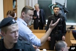 FILE - Russian opposition leader Alexei Navalny gestures while speaking in a court room in Moscow, Russia, Oct. 2, 2017. Navalny is currently serving a 20-day jail term for organizing an unsanctioned protest.