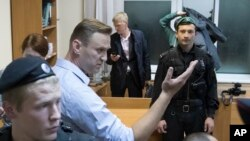 Russian opposition leader Alexei Navalny gestures while speaking in a court room in Moscow, Oct. 2, 2017. A Moscow court on Monday sent Navalny to jail for 20 days for calling for an unsanctioned protest.