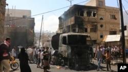 Warga berkumpul di sekitar truk minyak yang terkena tembakan dalam pertempuran antara pasukan Sunni dan pemberontak Syiah di kota Taiz, Yaman (25/5). (AP/Abdulnasser Alseddik)
