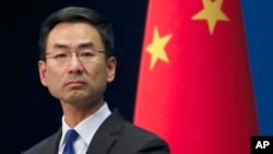 Chinese Foreign Ministry spokesman Geng Shuang listens a question from a reporter during a daily briefing at the Ministry of Foreign Affairs office in Beijing, Wednesday, March 18, 2020.