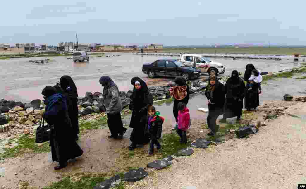 Syrian civilians cross from rebel-held areas in Idlib province into regime-held territories on through the Abu Duhur crossing.