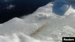 Científicos utilizan una regla para medir los fragmentos del meteorito encontrados alrededor del lago.