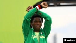 Silver medalist Feyisa Lilesa, of Ethiopia, acknowledges applause during an award ceremony as he crosses his wrists in an attempt to draw global attention to recent deadly protests in his home region, Oromia, after the men's marathon at the 2016 Summer Olympics