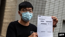 Pro-democracy activist Joshua Wong speaks to the media while holding up a bail document after leaving Central police station in Hong Kong on September 24, 2020, after being arrested for unlawful assembly related to a 2019 protest against a…