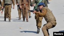 FILE - An Indian police officer aims his pellet gun towards demonstrators during a protest after Friday prayers in Srinagar, March 5, 2021.