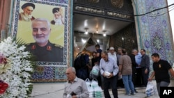 People leave a mosque at the conclusion of a mourning ceremony in a predominantly Iraqi neighborhood, south of Tehran, Iran, Tuesday, July 30, 2019. A poster of chief of the elite Quds Force of Iran's Revolutionary Guard Gen. Qassem Soleimani is…