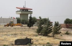 FILE PHOTO: Turkish soldiers stand on a watchtower at the Atmeh crossing on the Syrian-Turkish border, as seen from the Syrian side, in Idlib governorate, Syria, May 31, 2019.