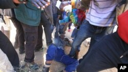 A police officer is assaulted by angry protesters in Harare, Monday, July, 4, 2016. (AP Photo/Tsvangirayi Mukwazhi)