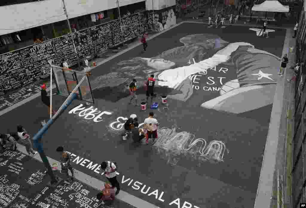 Artists put on the finishing touches on a giant painting of former NBA basketball player Kobe Bryant and his daughter Gianna at a basketball court in Taguig, south of Manila, Philippines.
